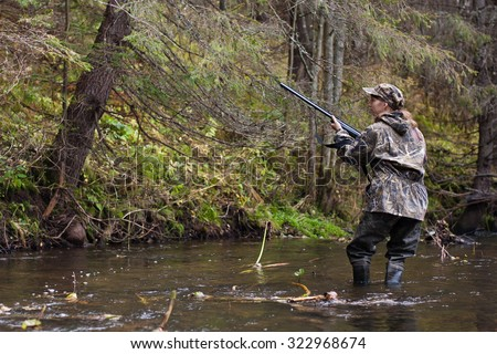 Woman hunter shooting on the river