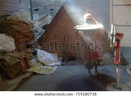 Woman husking rice in the light from a window