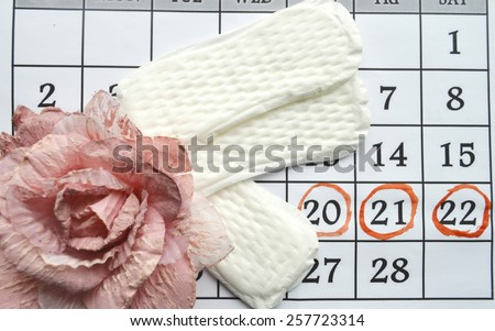 Woman hygiene protection, close-up.menstruation calendar with cotton tampons,orange Gerber,Sanitary pads on a red background - stock photo