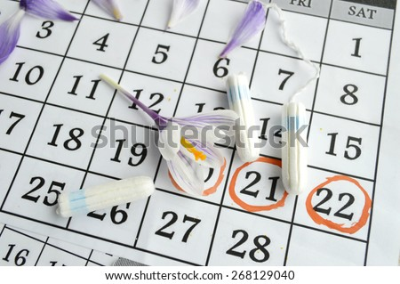 Woman hygiene protection, close-up.menstruation calendar with cotton tampons,orange Gerber,Sanitary pads.Spring flowers, femininity, tenderness, birth control pills - stock photo