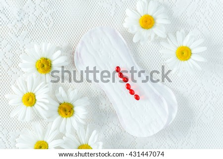 Woman hygiene protection, menstruation, sanitary pads on a white background, woman critical days, menstruation cycle, camomiles.