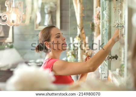 Woman in a accessory boutique arranging jewelry - stock photo