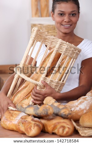 Woman in a bakery with a basket of bread - stock photo