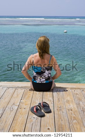 Woman in a Bathing Suit relaxing on a Caribbean Dock