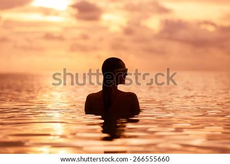 Woman in a beautiful sunset setting.  - stock photo