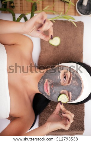 Woman in a beauty salon, wellness. Cosmetic procedure woman's face in the mask mitigating and cucumber slices on eyes