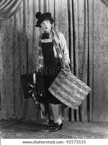 Woman in a beret holding a hat box and presents