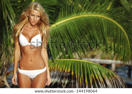 woman in a bikini on a background of palm trees - stock photo