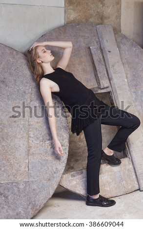Woman in a black clothes holding side of her head. - stock photo