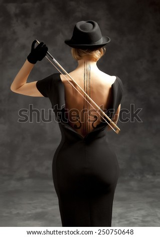 Woman in a black dress and black hat plays the violin - stock photo