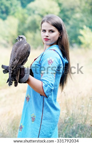 woman in a blue dress holding a falcon on his arm - stock photo