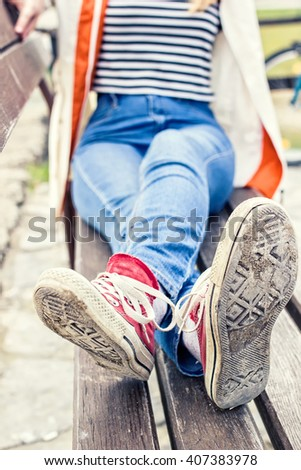 Woman in a blue jeans, striped t-shirt and a white jacket sitting on a bench, red canvas sneakers on her feet. - stock photo