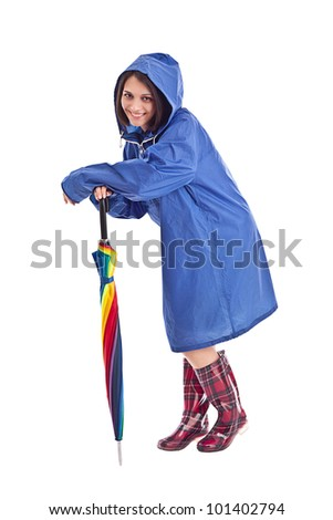 Woman in a blue mac with umbrella - stock photo