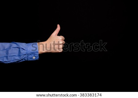 Woman in a blue shirt giving a thumbs up