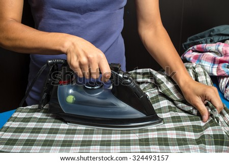 woman in a blue T-shirt ironing plaid shirt and other clothing using black iron on a dark background