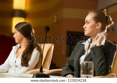 woman in a business suit sitting at a business conference at the table, on the table microphone and a glass of water - stock photo