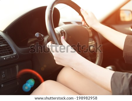 Woman in a car use audio system. Sunset shot with flares - stock photo