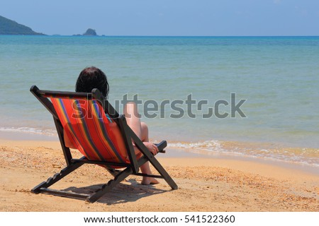 Woman in a chaise longue on the beach