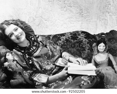Woman in a Chinese print dress lying on the sofa with her dolls and a book - stock photo