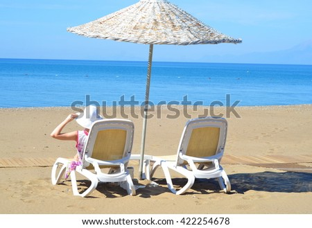 Woman in a deck chair under beach umbrella. Travel concept - stock photo