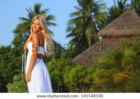 woman in a dress on a background of palm trees - stock photo
