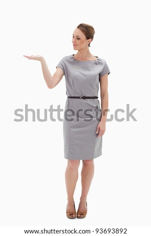 Woman in a dress presenting something with her hand against white background - stock photo