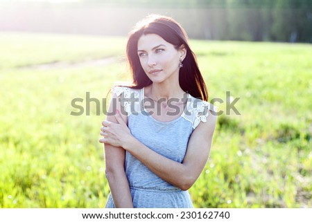 Woman in a dress standing in a field - stock photo