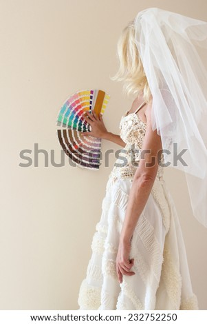 woman in a dress the bride chooses the color of the walls of their new home - stock photo