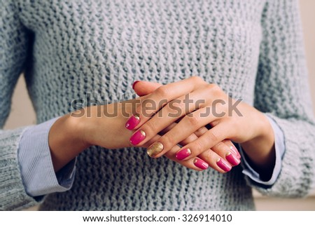 Woman in a gray knitted sweater shows pink and golden manicure closeup. - stock photo