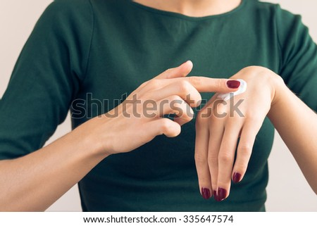 Woman in a green T-shirt and a maroon manicure applying hand cream - stock photo