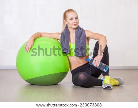 Woman in a gym resting after training  with fitness ball - stock photo