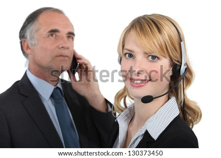 Woman in a headset next to a man with a cellphone - stock photo