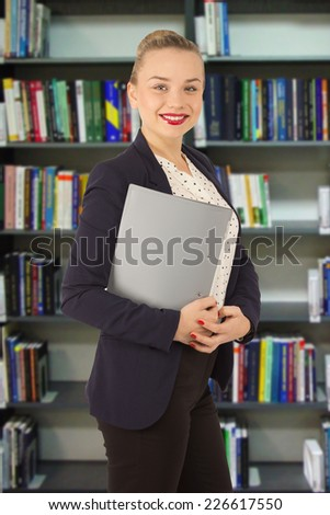 woman in a jacket with a folder in hands in a library
