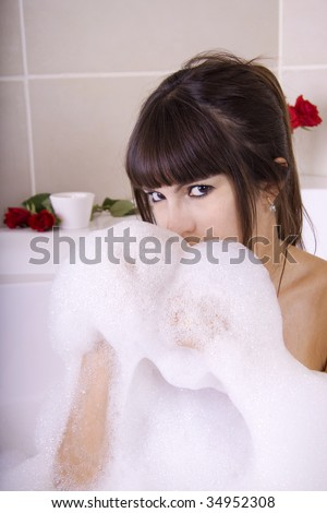 Woman in a jacuzzi is having fun with the foam