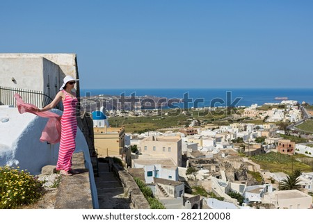 Woman in a long dress, a hat and scarf in his hands, looking at the beauty of island Santorini, Greece. - stock photo