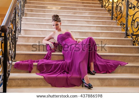woman in a long dress is sitting on the stairs in the hotel lobby - stock photo
