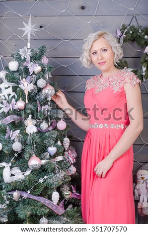 woman in a long pink dress decorated Christmas tree for Christmas and New Year