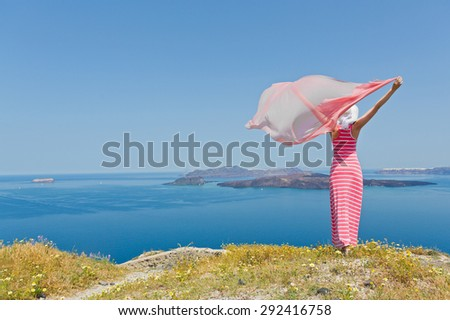 Woman in a long summer dress standing in a field of daisies, on the beach sea. Greece, Santorini - stock photo