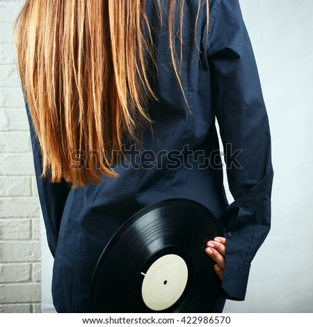 Woman in a man's shirt holding a vinyl - stock photo