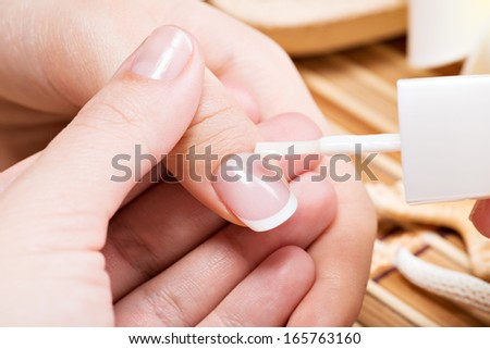 Woman in a nail salon receiving manicure. Beautician applying nail varnish on a thumbnail. - stock photo