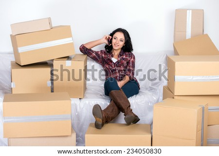 Woman in a new home with cardboard boxes, is sitting on covered sofa and speaking by phone. - stock photo