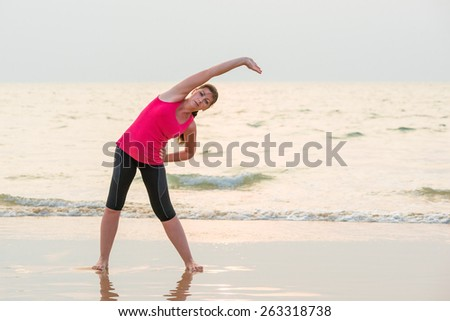 woman in a pink shirt doing exercises on the wet sand - stock photo