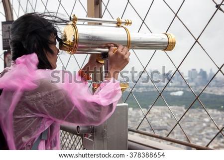 woman in a raincoat watching through binoculars near Eiffel Tower - stock photo