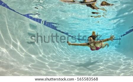 Woman in a Red Bikini Swimming Underwater in a pool - stock photo