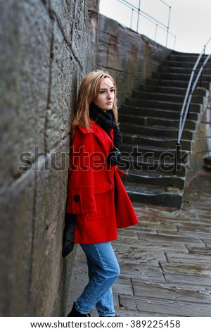 Woman in a red coat leaning on an old stone wall in the sleet and rain - stock photo