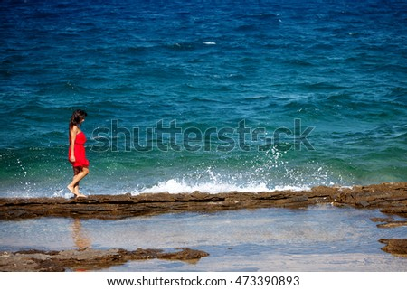 Woman in a red dress walks on the rocky beach