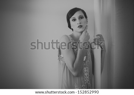Woman in a 1920's beaded flapper dress with a peacock feather hat. - stock photo