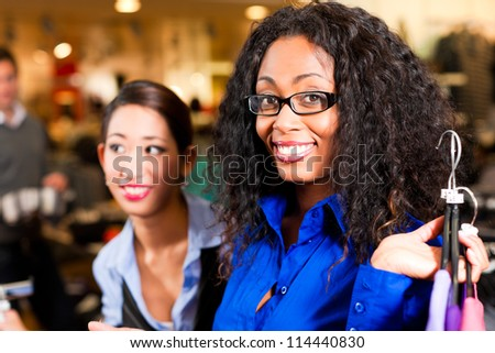 Woman in a shopping mall downtown looking for clothes - stock photo