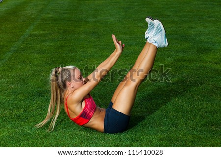 Woman in a sports suit doing exercises on a green field stadium - stock photo