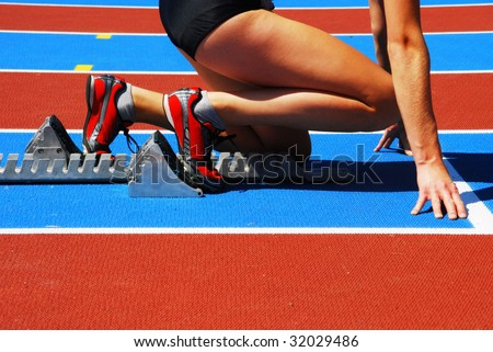 Woman in a starting block on an athletic field - stock photo
